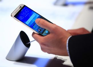 Пользователь держит в руке смартфон HTC One M9 // bloomberg.com